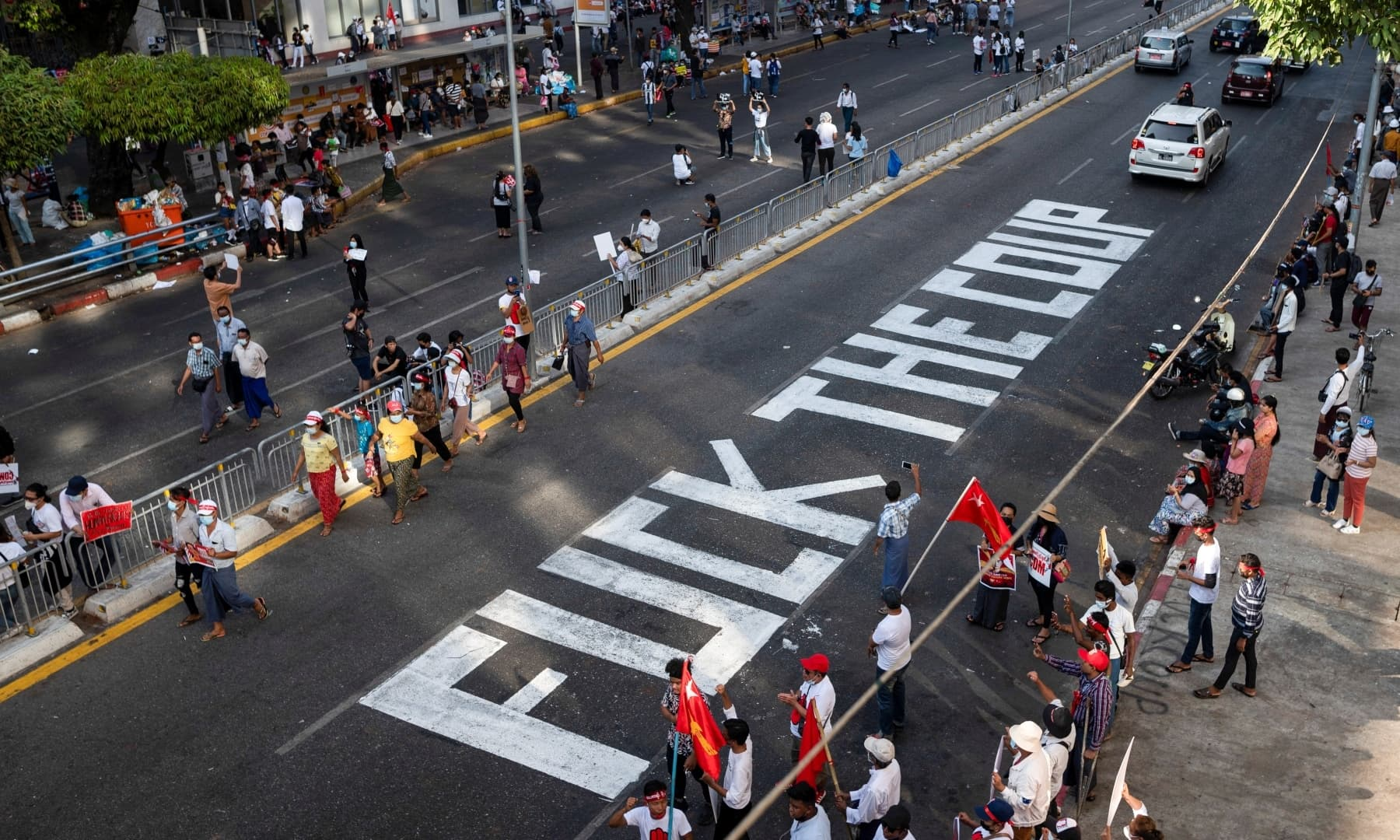 Demonstrators stand next to a writing on the street during a protest against the military coup in Yangon, Myanmar, February 17. — Reuters