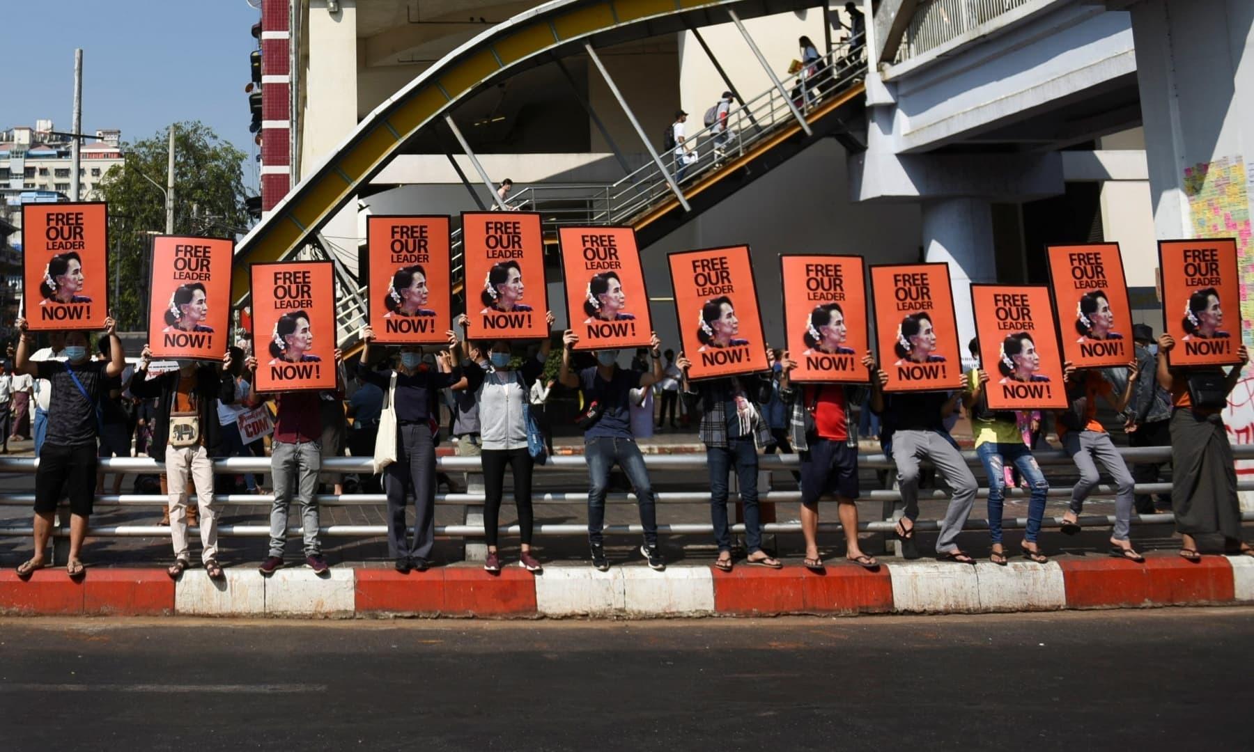 عوام نے احتجاج کے دوران فوج مخالف اور آنگ سان سوچی کے پورٹریٹ لے کر کھڑے ہیں—فوٹؤ: رائٹرز
