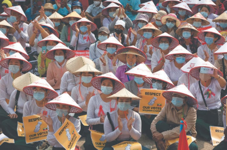 MANDALAY: Myanmar women, in traditional hat, occupy a street during a demonstration against the military coup on Thursday.—AFP