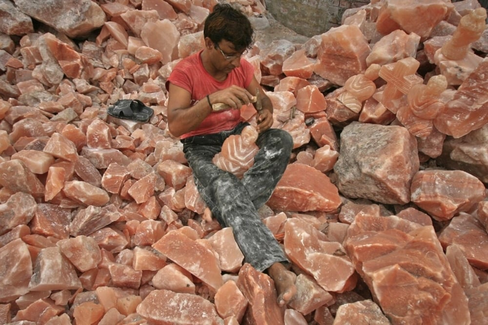 A man applies the final touches to a sculpture made from Himalayan pink rock salt on the outskirts of Lahore. — Reuters