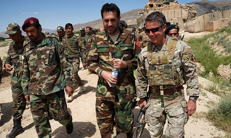 In this photo taken on June 6, 2019, commander of US and Nato forces in Afghanistan General Scott Miller (R) walks with Afghanistan's acting Defence Minister Asadullah Khalid (C) during a visit at the Afghan National Army (ANA) checkpoint in Nerkh district of Wardak province in west Kabul. — AFP/File