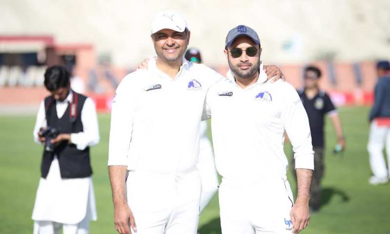 SAPM Zulfiqar Bukhari, captain of Gwadar Dolphins and PCB Chief Executive Wasim Khan, captain of Showbiz Sharks, stand together on Gwadar Cricket Stadium's pitch. — Ministry of Overseas Pakistanis and HRD Twitter account
