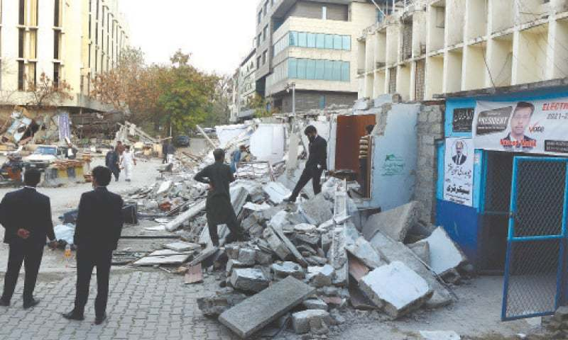 This Feb 8 file photo shows lawyers at the debris of their demolished chambers in Islamabad. — Mohammad Asim / White Star