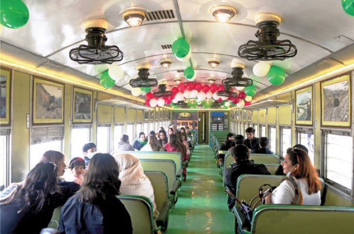 Visitors sit inside a coach after the inauguration of the Safari train at Golra Railway Station in Islamabad on Sunday. — Photo by Mohammad Asim