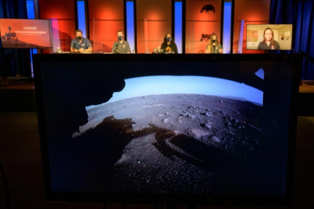 The first high-resolution, color image to be sent back by the Hazard Cameras (Hazcams) on the underside of Nasa's Perseverance Mars rover after its landing on February 18 is shown during a Nasa Perseverance rover initial surface checkout briefing at Nasa's Jet Propulsion Laboratory in Pasadena. —  Reuters