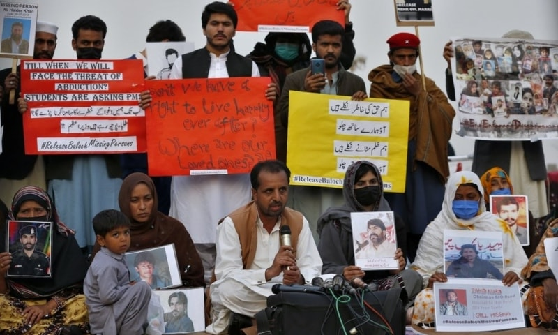 Nasrullah Baluch, centre bottom, leader of the Voice of Baloch Missing Persons, speaks while people hold placards and portraits of their missing family members during a press conference in Islamabad, Saturday, Feb. 20, 2021. — AP