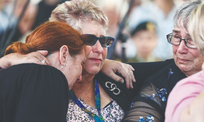 WOMEN embrace as they attend a service in memory of the 2011 earthquake victims in Christchurch.—AP