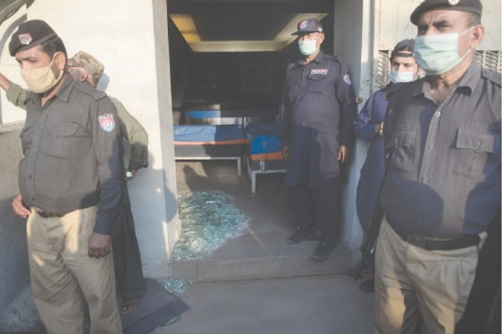 Policemen and guards stand where a walk-through gate once was after the attack on the main offices of the Jang-Geo media group on Sunday. The remains of the main glass door are also seen.—Dawn