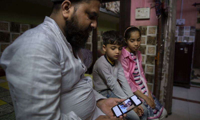 Haroon, holds a mobile phone as his nephew and niece look at the photograph of their father who was shot and killed by their Hindu neighbours during February 2020 communal riots, in North Ghonda, one of the worst riot affected neighborhood, in New Delhi, India. — AP