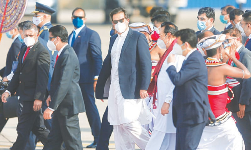 KATUNAYAKE (Sri Lanka): Prime Minister Imran Khan and his Sri Lankan counterpart Mahinda Rajapaksa walk side by side at the reception held at the airport after the Pakistani premier arrived here on Tuesday.—Reuters