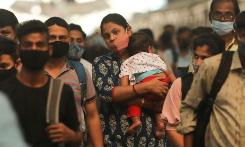 A woman carrying a child walks inside a railway station amidst the spread of the coronavirus disease in Mumbai, India, February 23. — Reuters