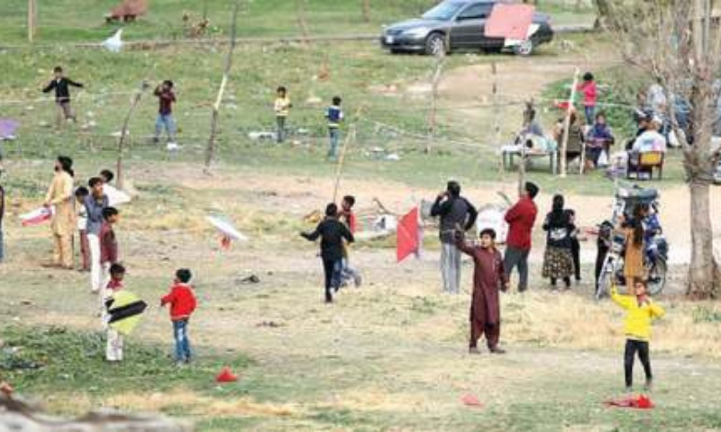 Youngsters fly kites on a ground in Rawalpindi on Friday despite a ban imposed by the city administration. — APP