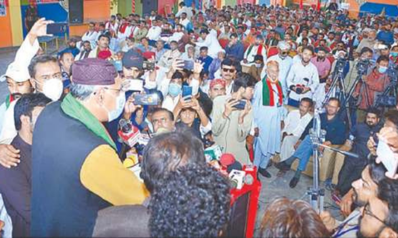 TANDO ALLAHYAR: Federal Minister for Planning Asad Umar speaking to PTI workers at a hall. — APP