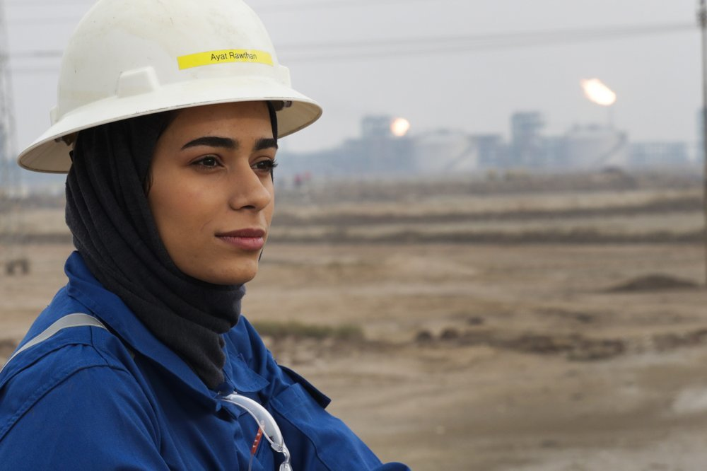 Ayat Rawthan, a petrochemical engineer, poses for a photo near an oil field outside Basra, Iraq.