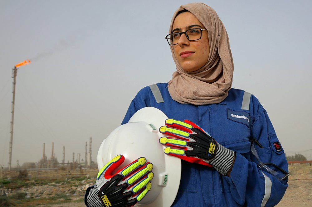 Zainab Amjad, a petrochemical engineer, poses for a photo near an oil field outside Basra, Iraq.