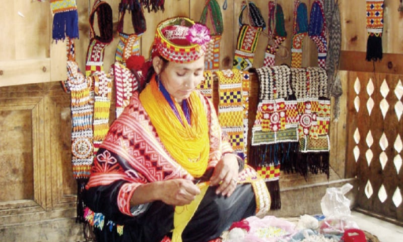 A women makes a traditional Kalash dress in her small shop. — Courtesy AKDN