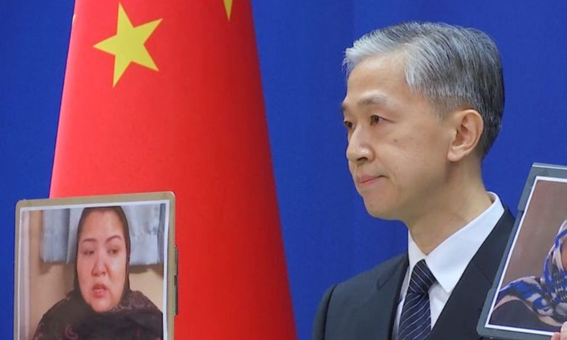 Chinese Foreign Ministry spokesman Wang Wenbin holds pictures while speaking during a news conference in Beijing, China, February 23. — Reuters