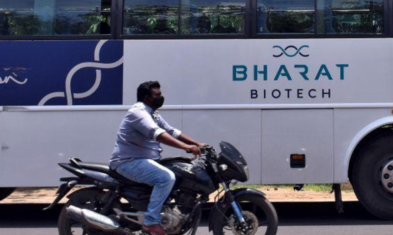 A man rides his motorcycle past a parked bus of Indian biotechnology company Bharat Biotech outside its office in Hyderabad, India. — Reuters/File
