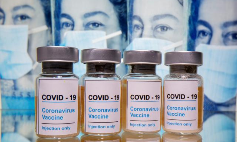 """Vials with a sticker reading, """"Covid-19 / Coronavirus vaccine / Injection only"""" are seen in front of displayed pound banknotes with Queen Elizabeth and masks in this illustration. — Reuters/File"""