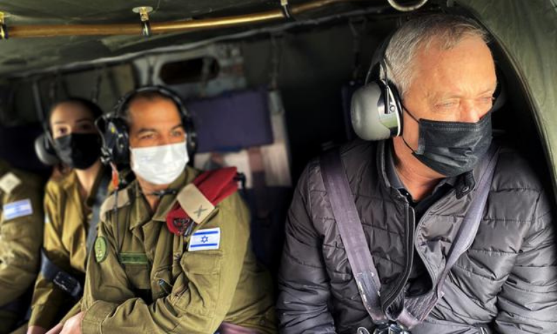 Israeli Defence Minister Benny Gantz wears a face mask as he looks out from the window of a helicopter during a tour of the Gaza border area, southern Israel on Tuesday. — Reuters
