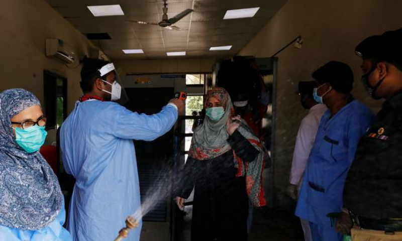 In this file photo, railway workers wearing protective gears measure the temperature and disinfect passengers before they board a train. — Reuters