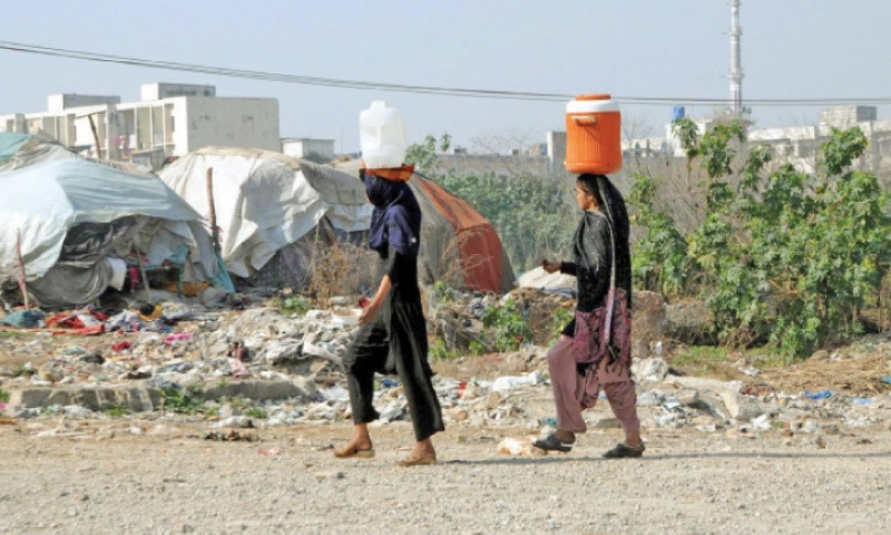 Girls head home after filling cans with water in I-9. The sector is one of the many areas in Islamabad facing water shortage. — Online/File