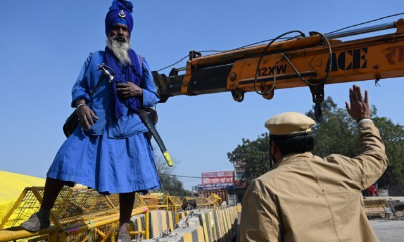 A Nihang, or a Sikh Warrior, watches as police set up road blocks at the Delhi-Haryana state border in Singhu. — AFP