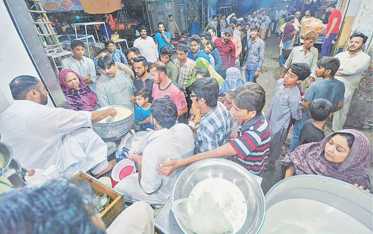 Men and women line up to purchase yogurt | Arif Ali/White Star