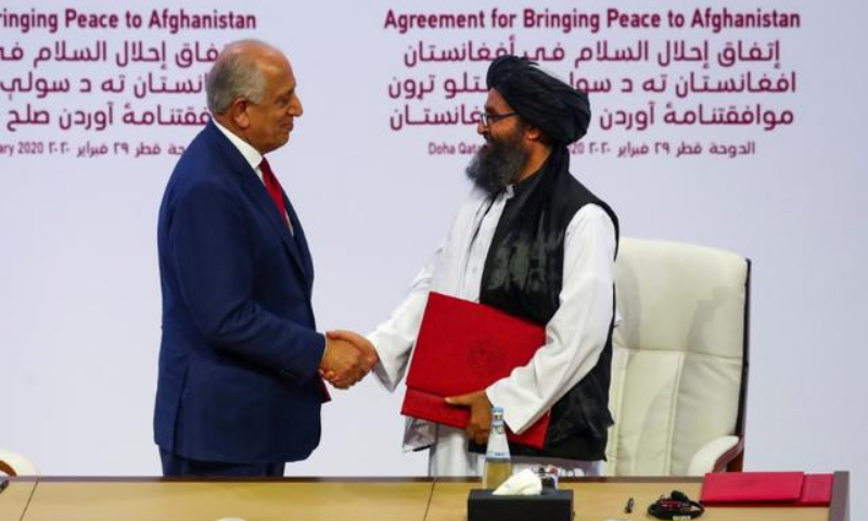In this Feb 2020 file photo, Mullah Abdul Ghani Baradar, the leader of the Taliban delegation, and Zalmay Khalilzad, US envoy for peace in Afghanistan, shake hands after signing an agreement at a ceremony between members of Afghanistan's Taliban and the US in Doha. — Reuters