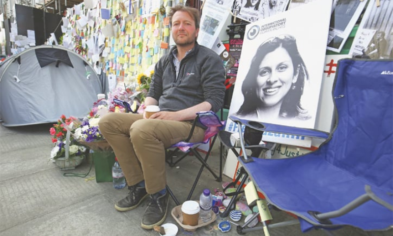 In this file photo, Richard Ratcliffe, the husband of detained Nazanin Zaghari Ratcliffe (seen in poster), sits outside the Iranian Embassy on the day he ended his 15-day hunger strike and his imprisoned wife also ended her own hunger in an Iran jail. — AP