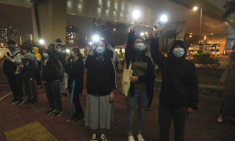 Supporters hold flash lights after activists charged with conspiracy were released on bail at a court in Hong Kong on March 5. — AP