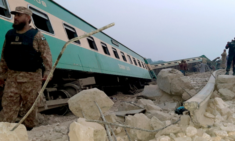 Army, police and rescue workers gather at the site of a derailed train near Rohri. — AP