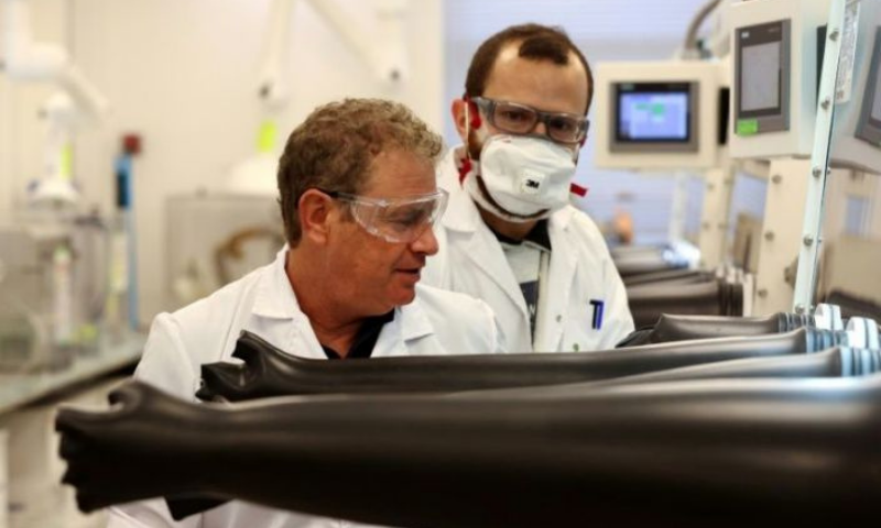 Israeli startup StoreDot founder Doron Myersdorf (L) with a colleague at the company that has developed ultra-fast rechargeable batteries. — AFP