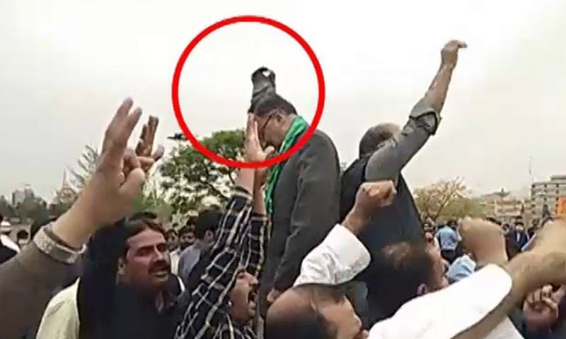Screenshot from a video clip from Saturday shows a shoe flying at PML-N leader Ahsan Iqbal. — DawnNewsTV