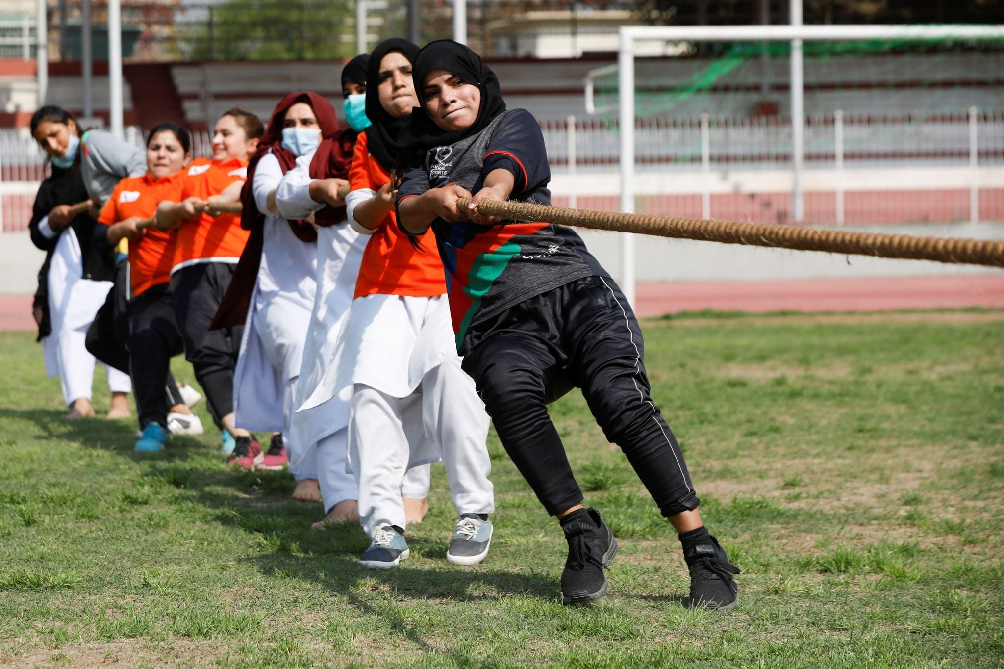 Participants react as they pull a rope during a sports event in connection with the International Women's Day celebrations in Peshawar, March 8. — Reuters