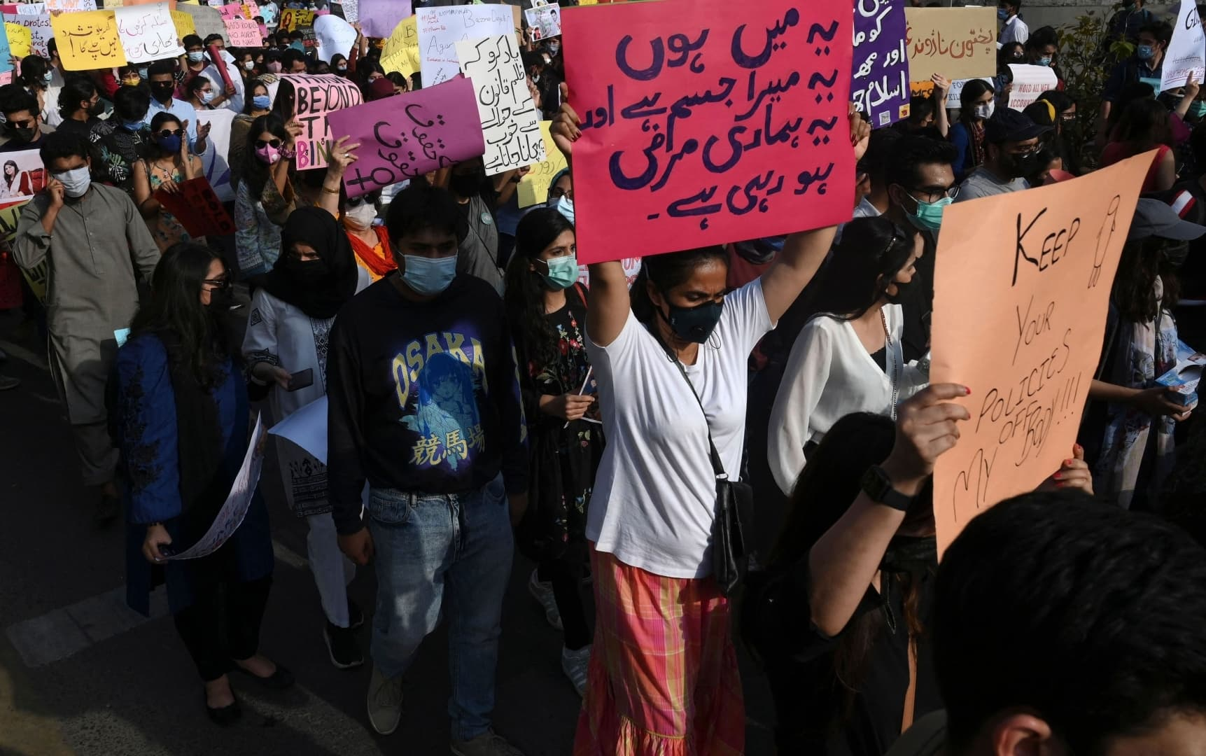 Participants of the Aurat March carry placards as they march during a rally to mark International Women's Day in Lahore on March 8. — AFP