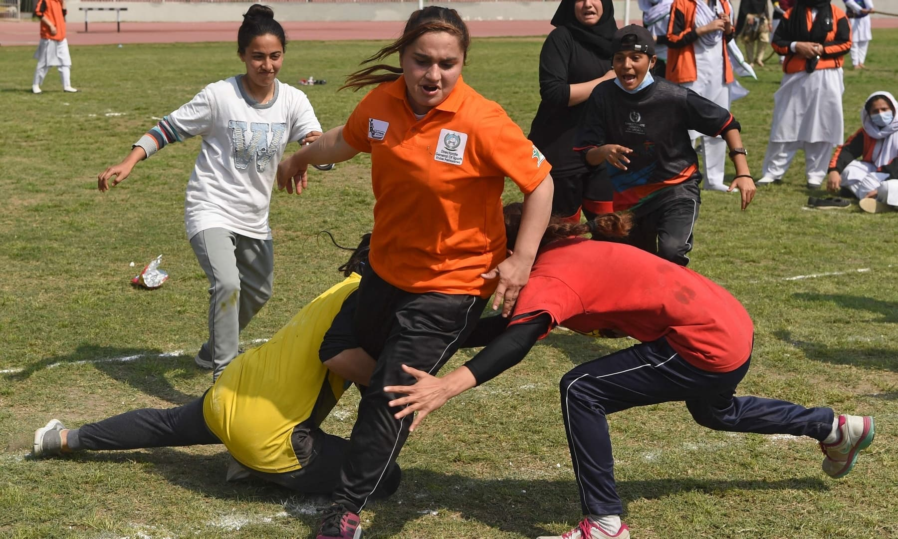 Students play football in a field in Peshawar on March 8 on the International Women's day. — AFP