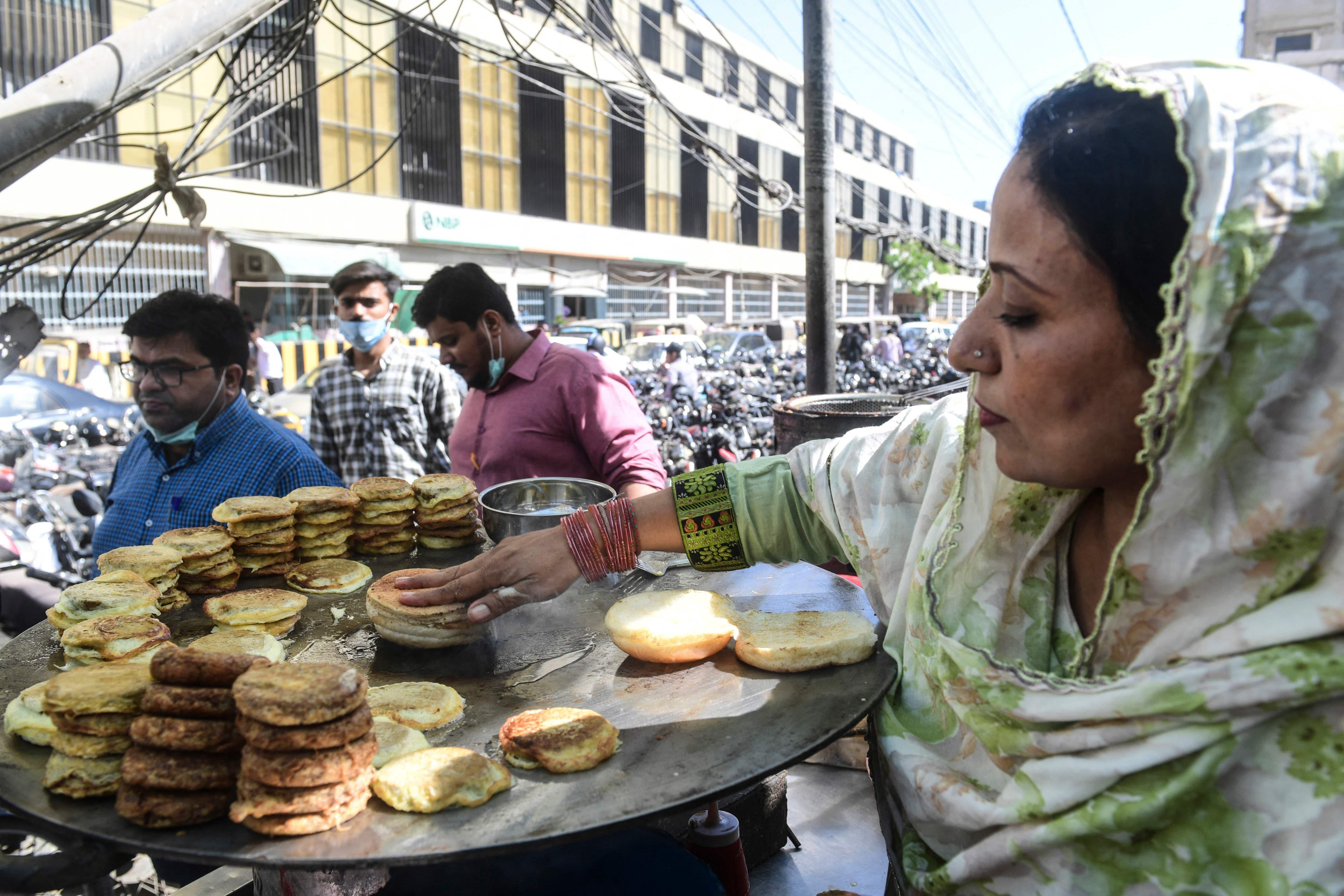 Street vendor Lubna Raheem (R) prepares snacks for customers at her roadside stall on International Women's Day in Karachi on March 8. — AFP