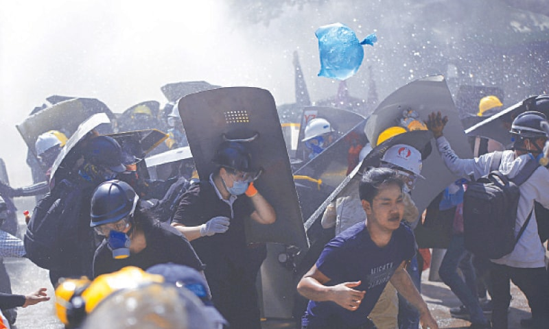 YANGON (Myanmar): Protesters are dispersed as riot police fire tear gas during a demonstration here on Monday.—AP