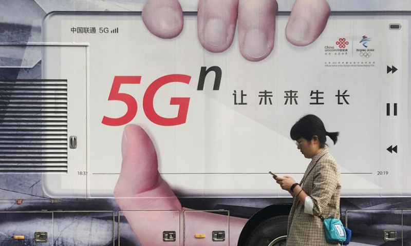 A woman using her mobile phone walks past a vehicle covered in a China Unicom 5G advertisement in Beijing, China. — Reuters/File