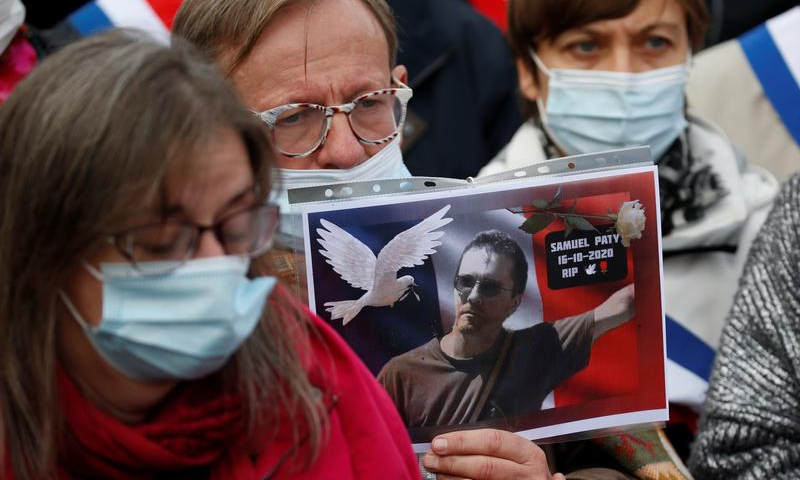 A person holds a picture of Samuel Paty, the French teacher who was beheaded on the streets of the Paris suburb of Conflans St Honorine, during a tribute at the Place de la Republique, in Lille, France. — Reuters/File