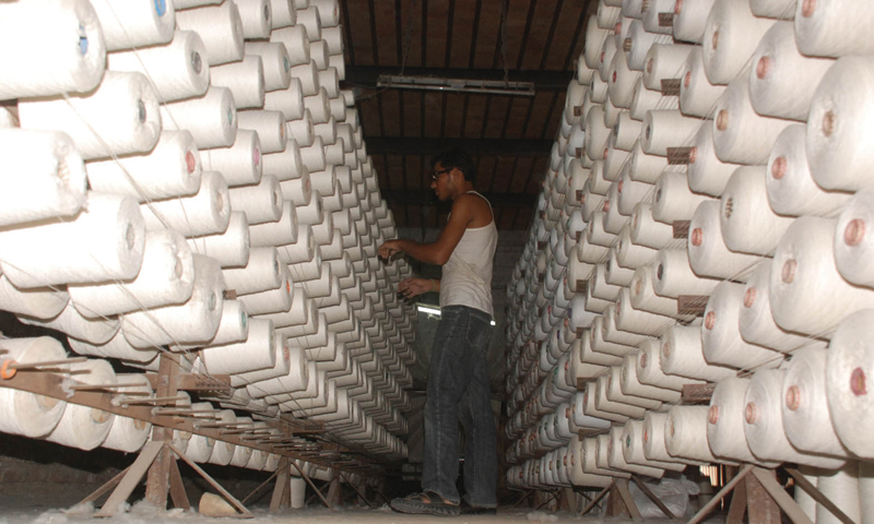 FAISALABAD: An employee works on spindles in a yarn factory. —INP/File