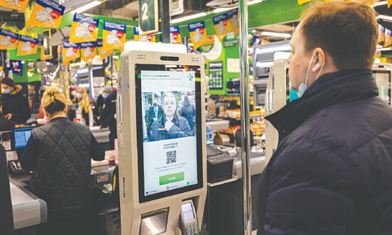 MOSCOW: A representative of the X5 group shows how the facial recognition payment system works, at one of his group's supermarkets.—AFP