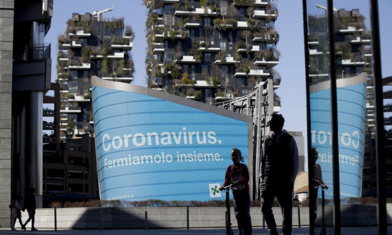 A man and a girl on a scooter are backdropped by a Lombardy region campaign advertising reading in Italian ' Coronavirus let's stop it together ', at the Porta Nuova business district in Milan, Italy, March 11, 2020. — AP/File