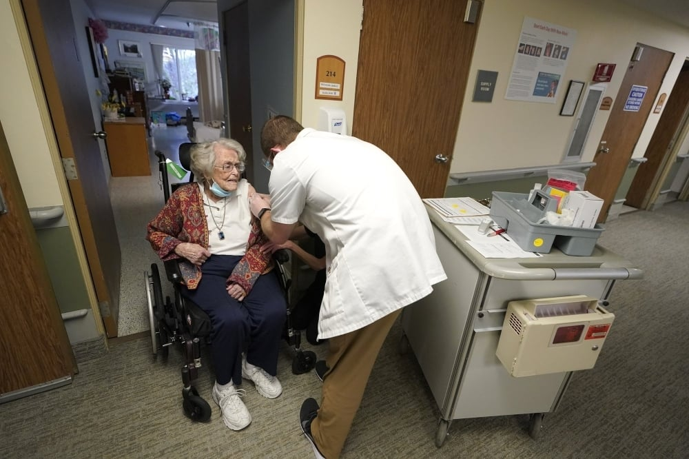 Jean Allen, 96, left, receives the first shot of the Pfizer vaccination, from a Walgreens Pharmacist, right, at Queen Anne Healthcare, a skilled nursing and rehabilitation facility in Seattle, Jan 8. — AP