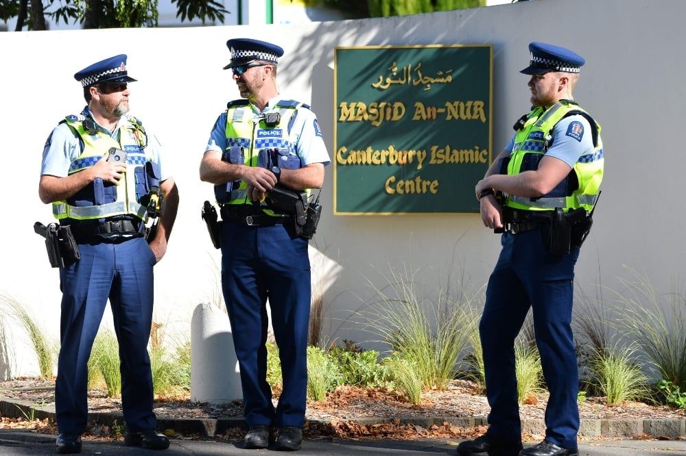 Police officers stand guard outside Al Noor Mosque in Christchurch on March 13. — AFP