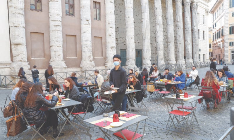 PEOPLE sit at outdoor tables in Rome before tighter coronavirus restrictions on restaurants and bars are enforced.—Reuters