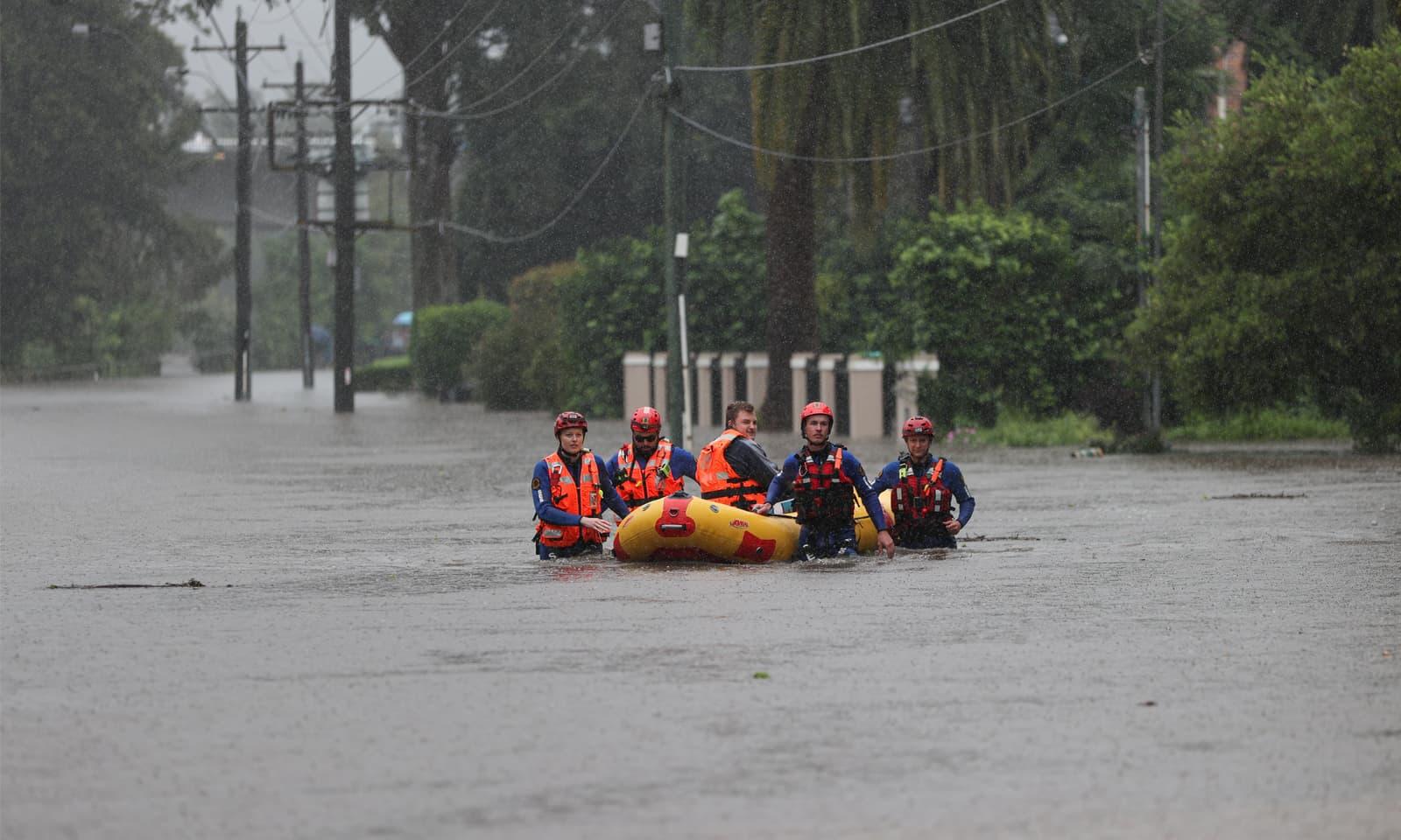 امدادی رضاکار سیلاب میں پھنسے افراد کو محفوظ مقام پر منتقل کر رہے ہیں — فوٹو: رائٹرز