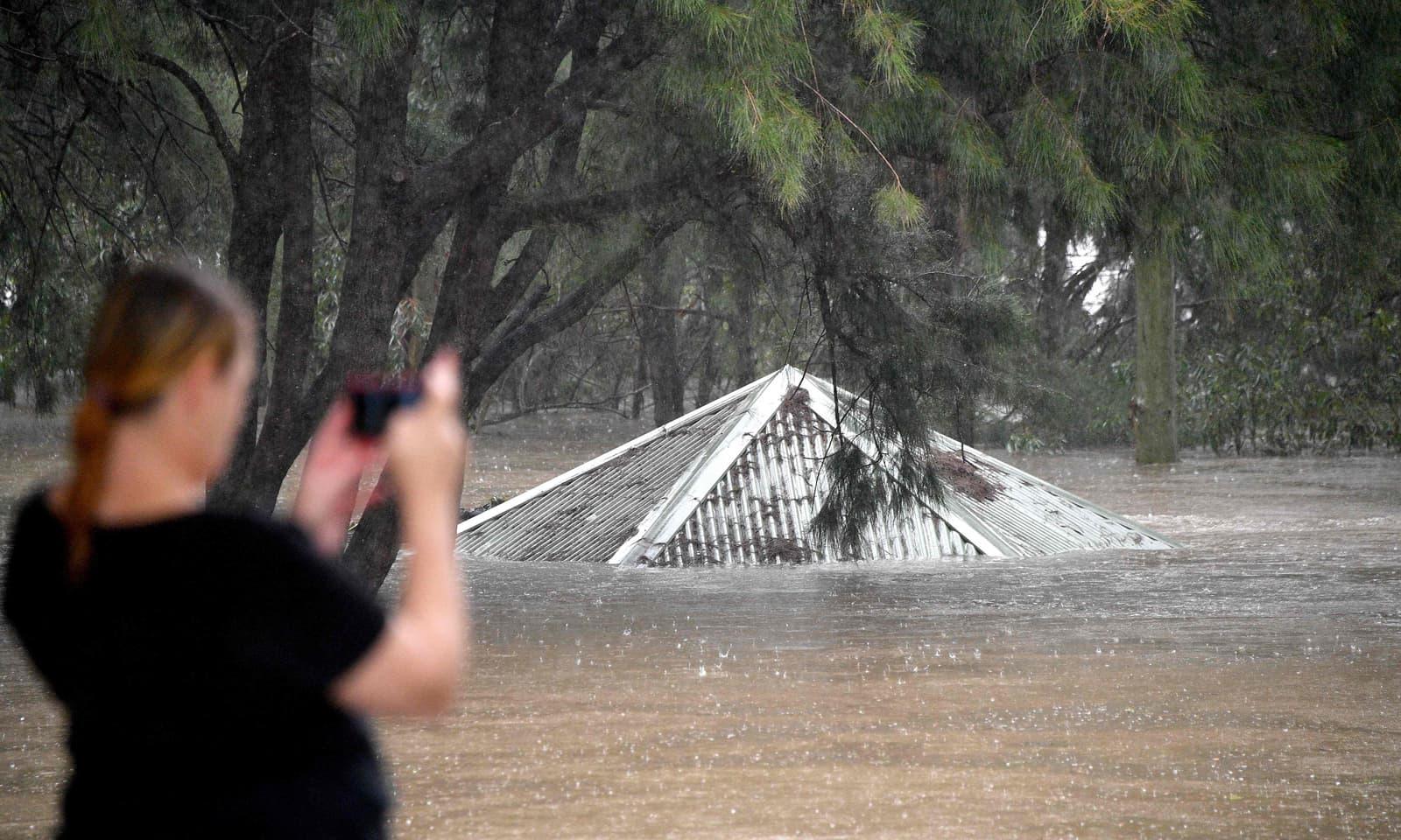 ایک خاتون سڈنی میں بدترین سیلاب کے بعد ڈوبے ہوئے پارک کی تصویر لے رہی ہیں— فوٹو: اے ایف پی