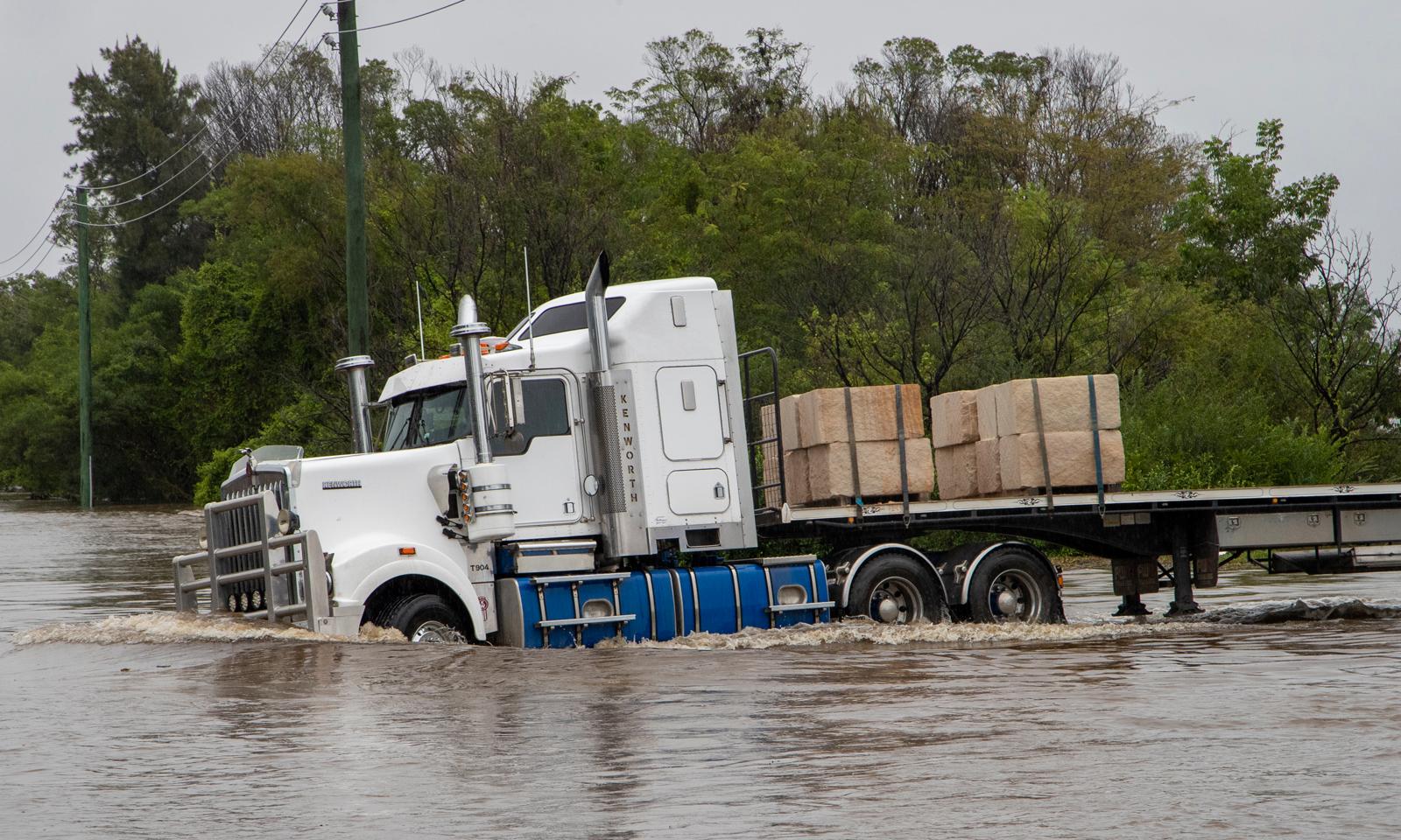 ایک ٹرک سیلابی پانی کے ریلے سے نکلنے کی کوشش کررہا ہے— فوٹو: اے پی